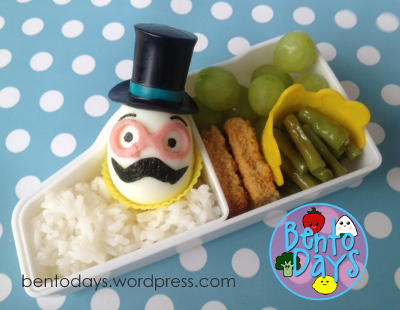 Cute lunch bento for kids. Moustache (mustache) lunch bento - boy themed. Made with hard boiled egg and nori, top hat decoration
