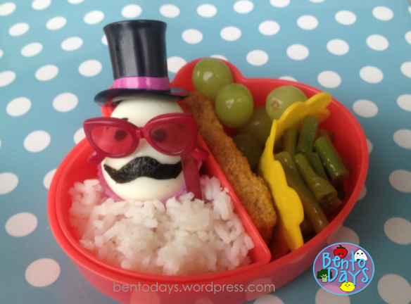 Cute lunch bento for kids. Moustache (mustache) lunch bento - girl themed. Made with hard boiled eggs and nori, top hat and sunglasses decoration