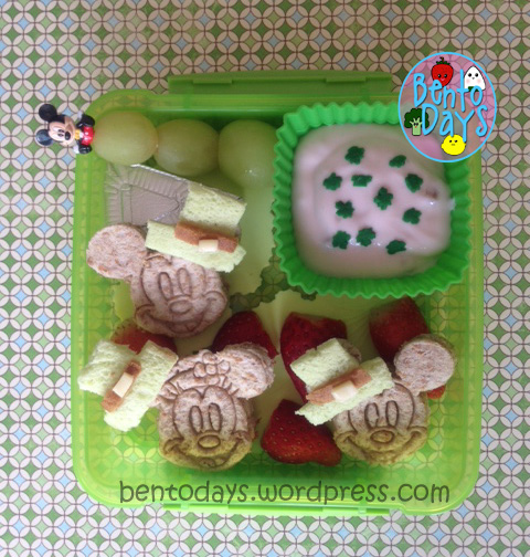 cute lunch bento for kids for St Patrick's Day lunch or party. Mickey and Minnie wearing green leprechaun hats.